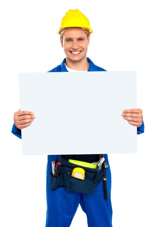 Confident construction worker holding blank billboard isolated over white background photo
