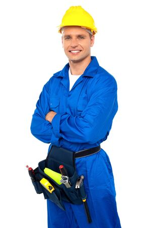 Young contractor with tool set and arms crossed isolated over white photo