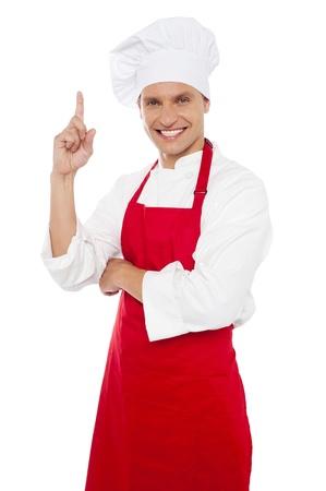 delantal: Cocinero sonriente feliz que muestra el dedo �ndice y mirando a la c�mara Foto de archivo