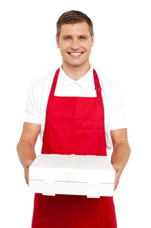 A chef in red uniform offering you a pizza box. Smiling at camera photo