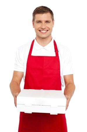 pizza box: Un cocinero con el uniforme rojo que le ofrece una caja de pizza. Sonriendo a la c�mara