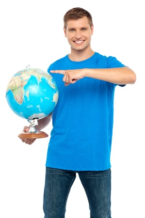 Casual cool guy pointing at rotating globe isolated over white background photo
