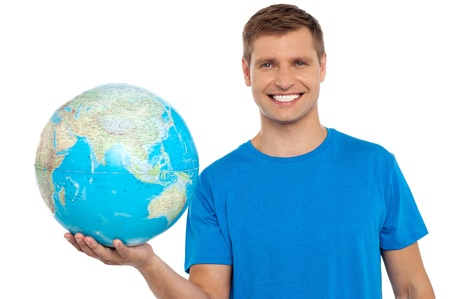 Young cheerful man holding a globe in his hand isolated over white background photo