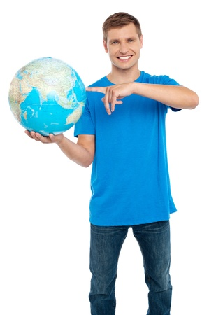 Smart guy pointing at the globe. Dressed in casuals. Isolated over white photo