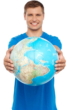 Casual young guy presenting globe. Golding it safely with both the hands photo