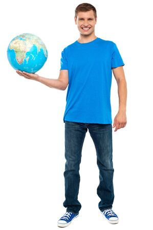 Trendy casual guy posing with a globe. Full length portrait photo
