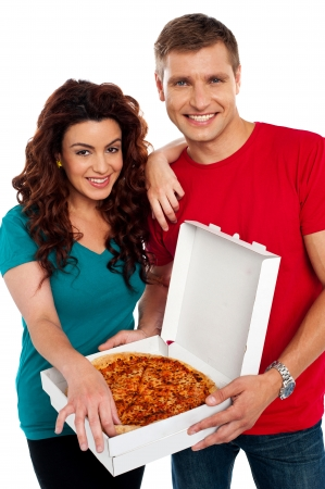 Cheerful love couple enjoying pizza together isolated against white background photo