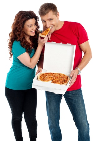 Girl sharing a pizza piece with her boyfriend. making him eat from her hands. Love couple photo