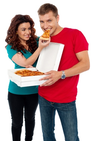 Caring girlfriend making her boyfriend eat pizza. Adorable love couple photo