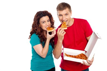 Adorable young couple relishing yummy pizza. Indoor studio shot photo