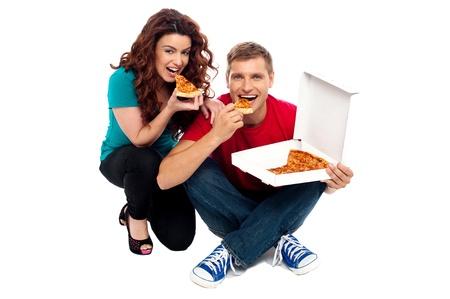 Young couple sitting on floor and enjoying yummy pizza photo