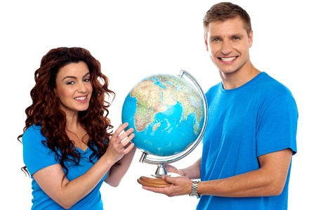 Joyful couple holding globe and smiling at camera. Isolated over white background photo