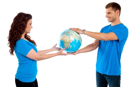 Causal young couple holding globe together and looking at each other photo