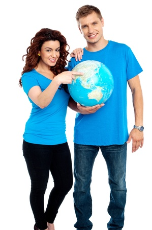 Couple posing for a picture with globe in hand. All on white background photo