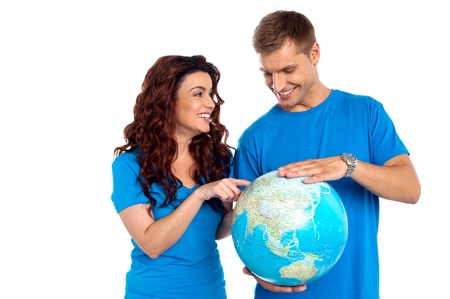 Couple discussing about specific country while points at it. All on white background Stock Photo - 15030537