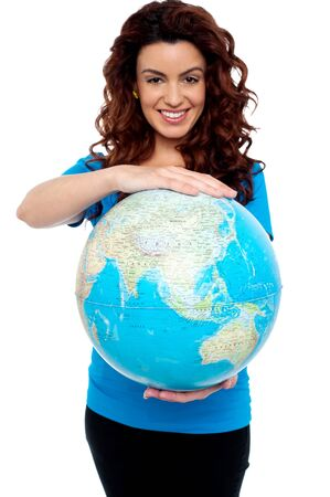 Cheerful girl holding globe safely with both hands. Holding from top and bottom. photo