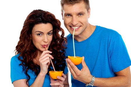 sipping: Closeup of couple cuddling and sipping orange juice. Smiling at camera
