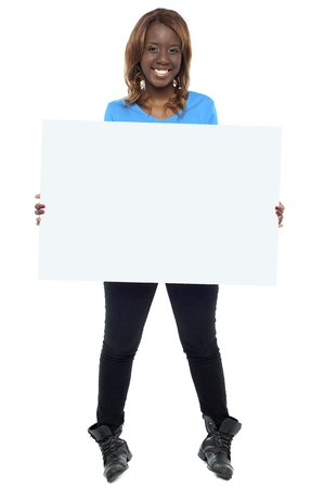 African girl model holding blank billboard. Full length shot photo