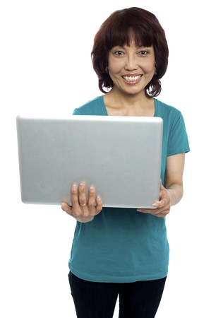Casual asian girl holding laptop isolated against white background photo