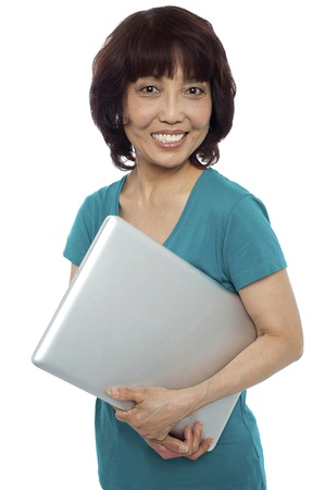 Casual woman carrying her laptop and smiling at camera Stock Photo - 15138498