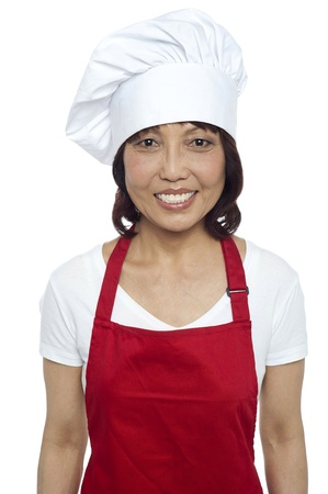 Young smiling female chef wearing red apron and toque photo