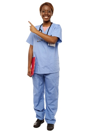 enfermera con paciente: Mujer m�dico que se�ala en espacio de la copia, la celebraci�n de portapapeles. Retrato de cuerpo entero