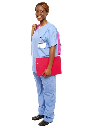 Junior female doctor under training. Ready to attend class holding backpack and clipboard Stock Photo - 15137711