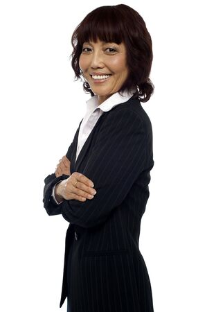 Side pose of matured asian female consultant posing with arms crossed photo