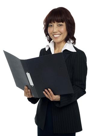 Secretary holding opened binder, smiling. Isolated against white background Stock Photo - 15137948