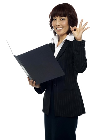Lady consultant satisfied with the report, gesturing okay sign Stock Photo - 15137872