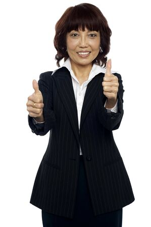 yup: Satisfied asian businesswoman showing double thumbs-up to you Stock Photo