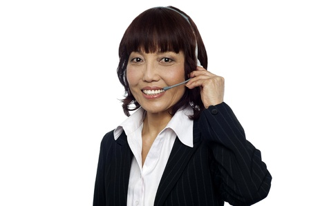 Cheerful asian customer support operator wearing headsets isolated over white background photo
