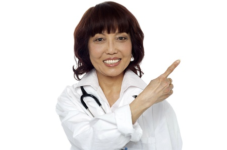 Matured surgeon pointing at the copy space isolated over white background photo