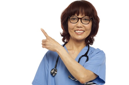 Asian nurse pointing at the copy space. All on white background photo