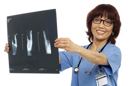 Doctor holding x-ray report. Analyzing it. All on white background photo