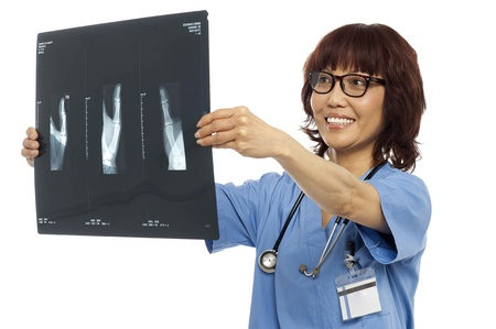 Female doctor reviewing x-ray report of her patient. Indoor shot photo