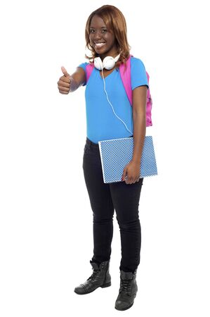 Trendy confident college showing thumbs up to camera. Enjoying music through headphones Stock Photo - 15137865