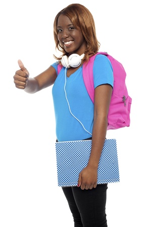 Stylish african college girl showing thumbs up to camera. All on white background photo