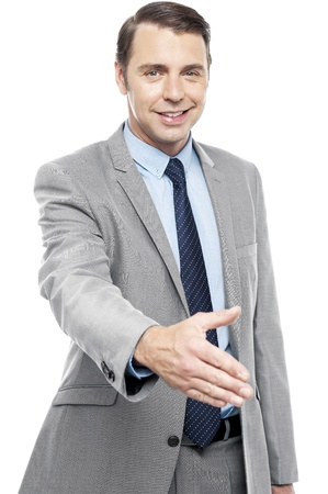 Young smiling male executive welcoming you with a handshake isolated against white background photo