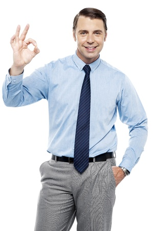 subordinates: Team leader gesturing okay sign to his subordinates. All against white background Stock Photo