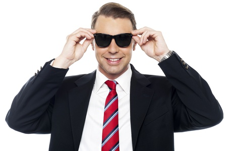 Stylish handsome businessman wearing shades looking at camera photo