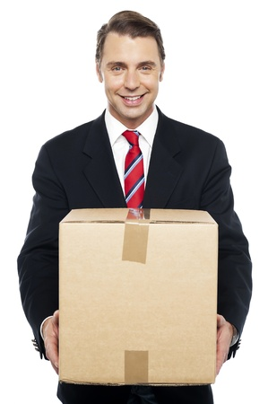 well dressed  holding: Smiling businessman holding cardboard box, being asked to change his cube Stock Photo
