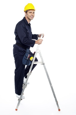 Industrial employee stepping up the ladder and looking at you photo