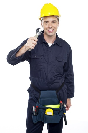 Smiling repairman holding out screwdriver from among his tool kit photo