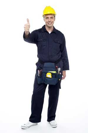 Young smiling industrial engineer showing thumbs up over white background Stock Photo - 15243598