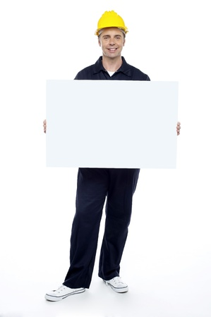 Full length portrait of smiling young repairman holding blank billboard photo
