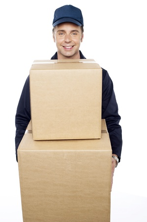 Young man carrying huge cardboard boxes. Delivered at your doorstep photo