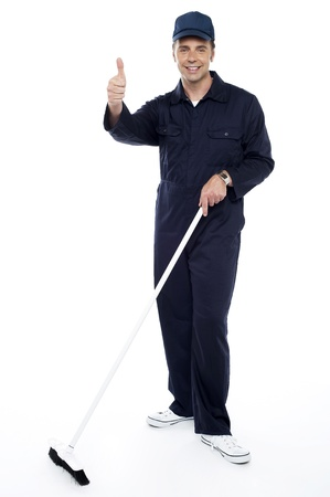 yup: Cleaning guy holding broom and showing thumbs up to camera. Full length shot Stock Photo