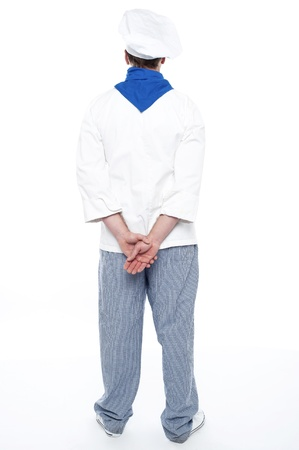 Rear view of male chef posing with hands behind isolated over white photo