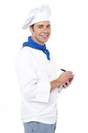 the recipe to write down: Chef taking down the order from customers, writing on notepad Stock Photo